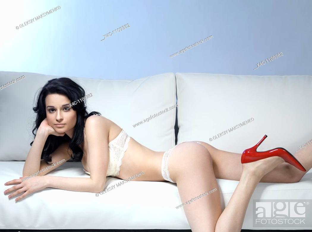 Stock Photo: Young beautiful woman in lingerie and red stiletto shoes lying on a sofa.