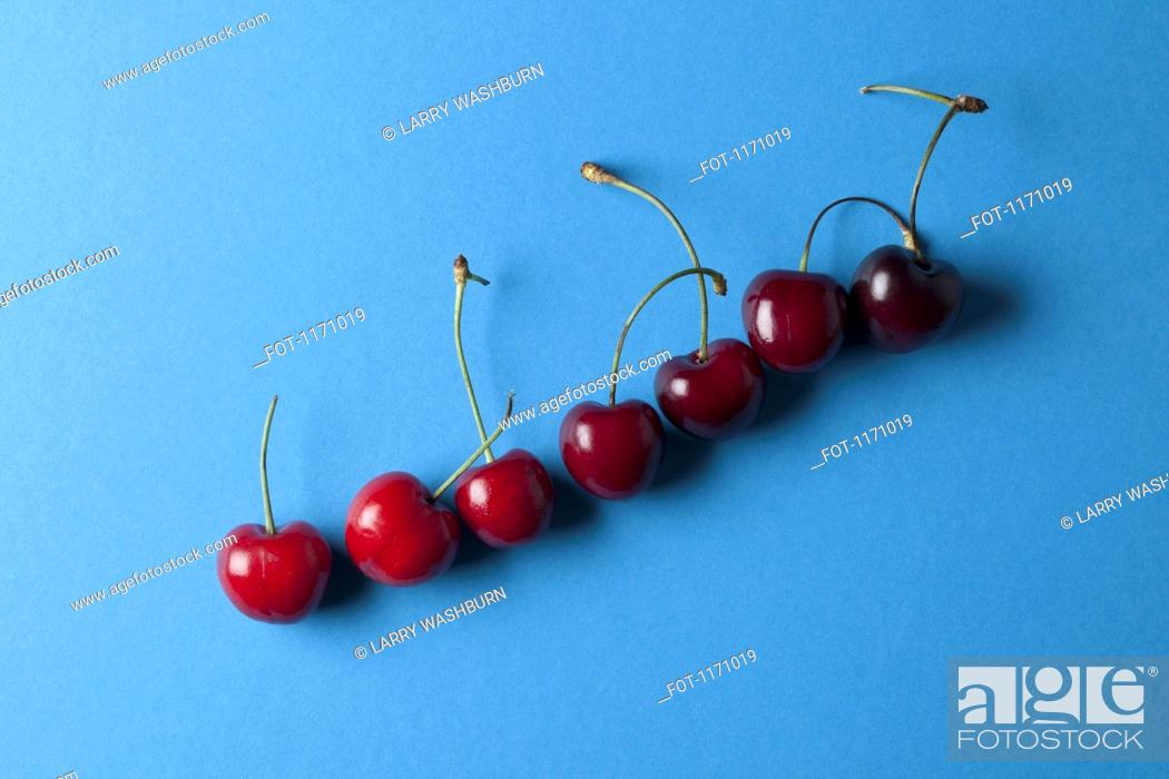 Stock Photo: A row of ascending cherries with stems.