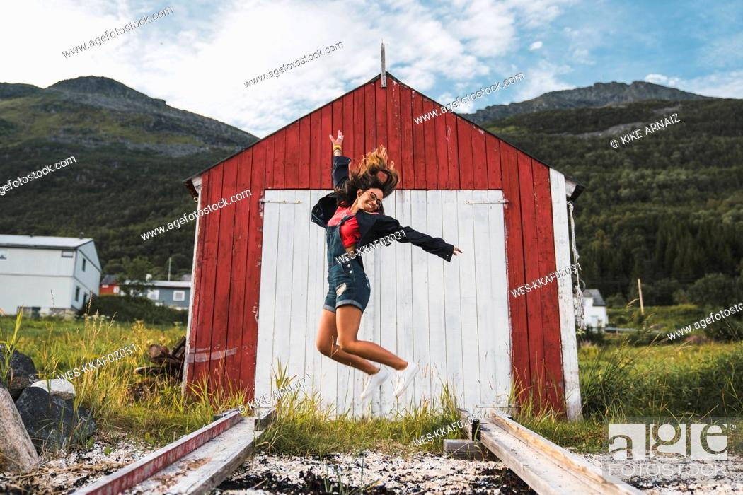 Photo de stock: Young woman jumping in front of red barn in Nothern Norway.