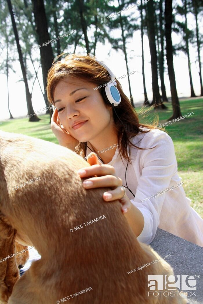 Imagen: Close-up of a young woman wearing headphones and stroking a dog.