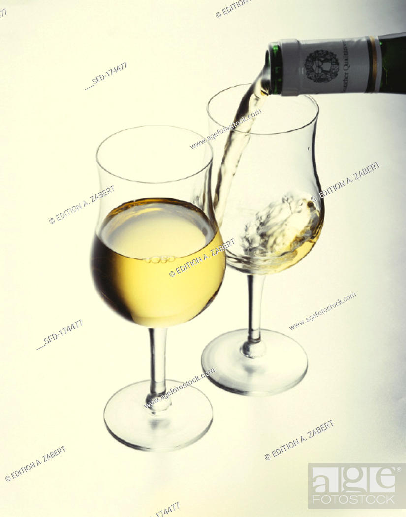 Stock Photo: Pouring white wine into a glass, filled glass in front.