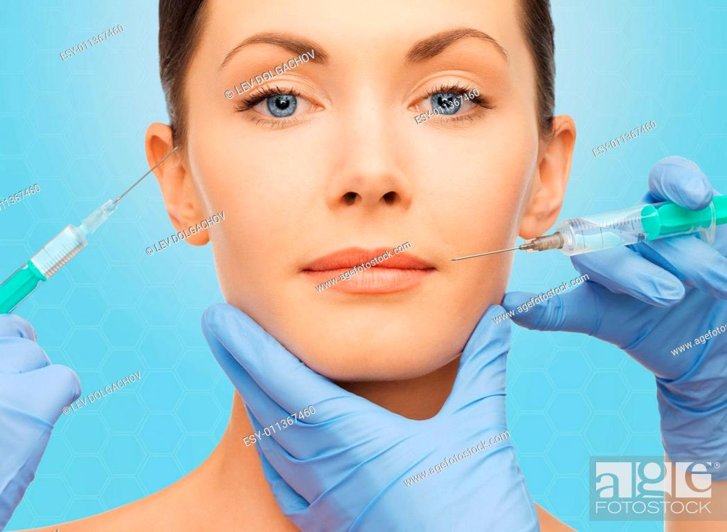 Stock Photo: plastic surgery, injections and beauty concept - beautiful young woman face and surgeon hands with syringes over blue background.