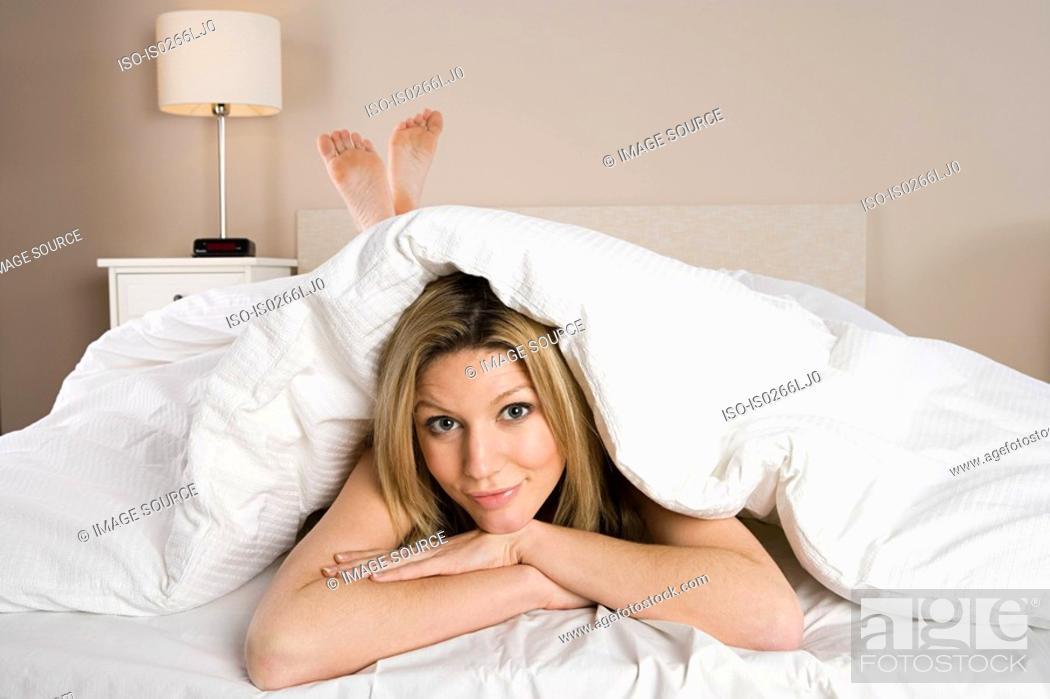 Stock Photo: Woman under duvet.