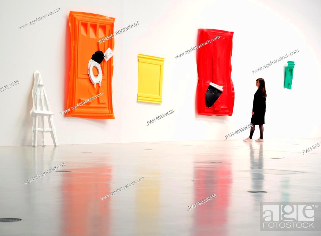 Portable Toilet Exhibition : A woman looks at art works made of parts of portable toilets at an