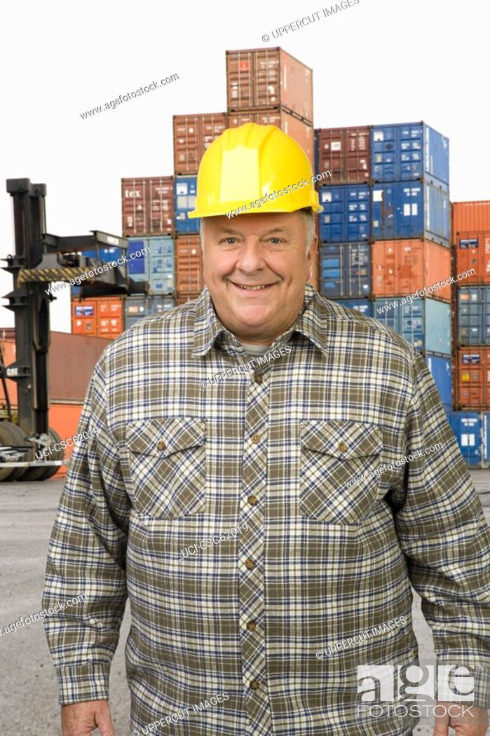 Stock Photo: Male dock worker in front of cargo containers.