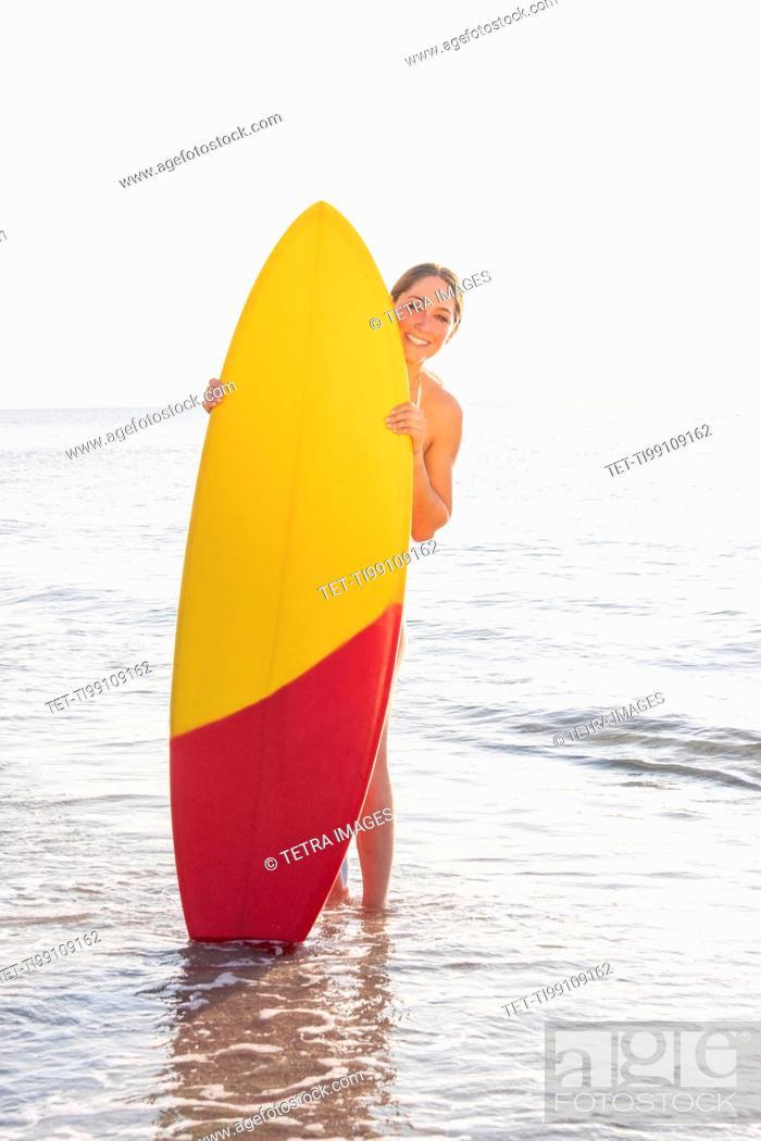 Stock Photo: Smiling woman peering around surfboard on beach.