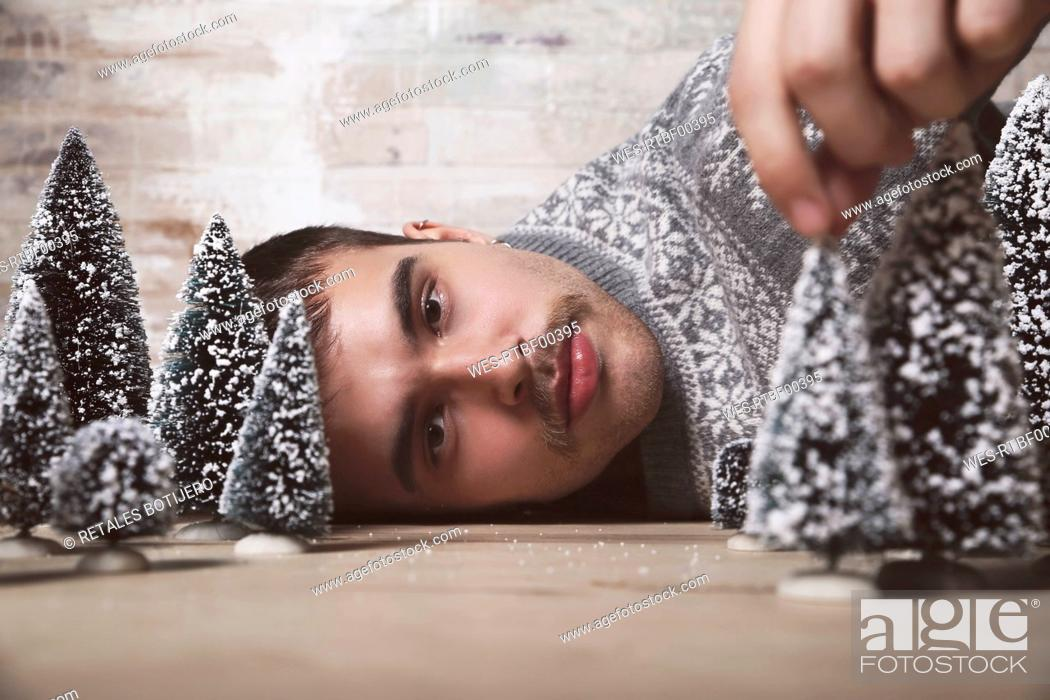 Stock Photo: Young man lying on the floor with Christmas tree decoration.