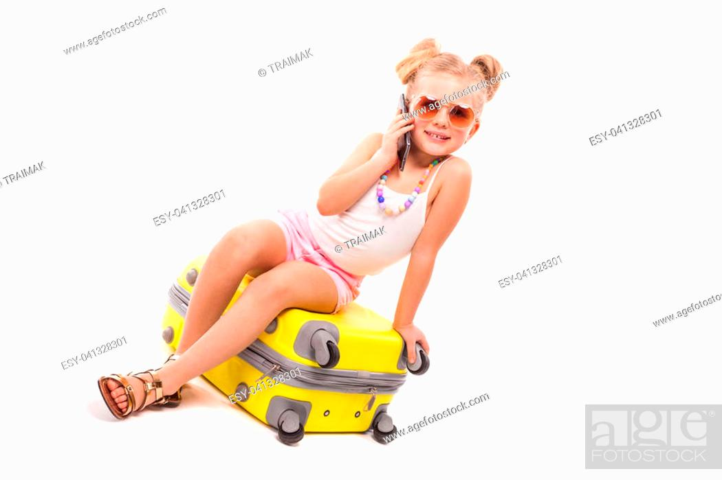 Stock Photo: Isolated on white, pretty little caucasian blonde girl in white shirt, pink shorts, sunglasses and sandals sit on the yellow suitcase, look at camera.