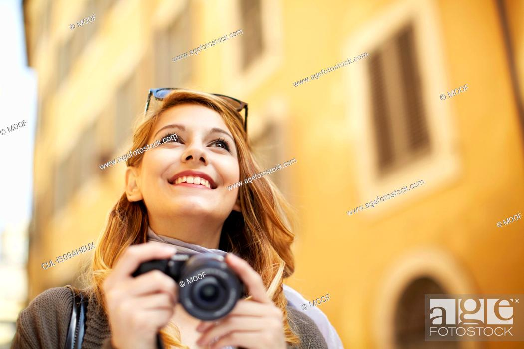 Stock Photo: Young woman with digital camera, Rome, Italy.