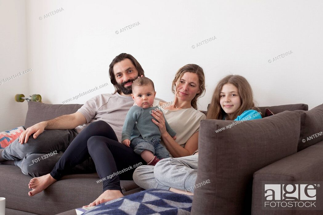 Stock Photo: Portrait of family with two children sitting on sofa in living room.