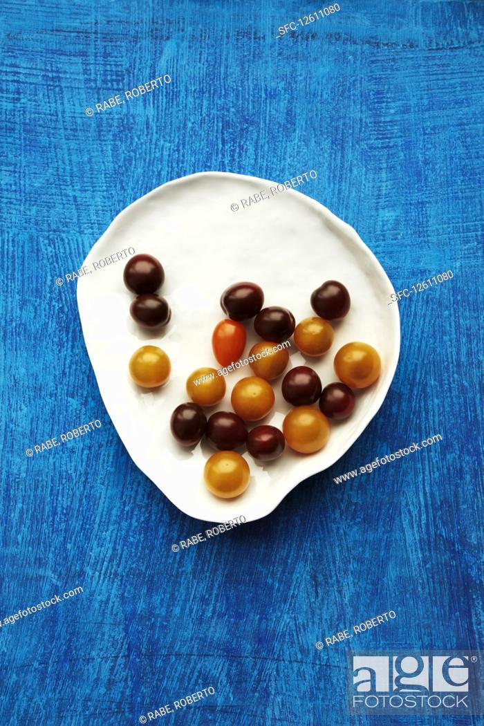 Imagen: Various cocktail tomatoes on a plate against a blue background.
