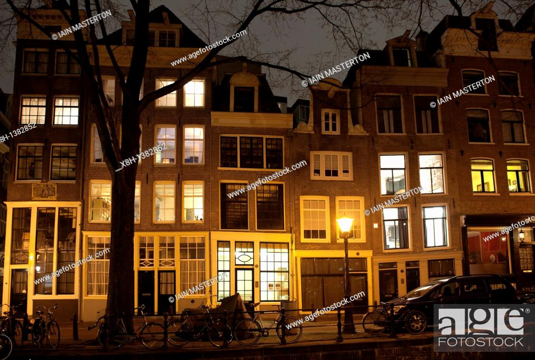 Stock Photo: Evening view of residential buildings beside canal in central Amsterdam The Netherlands.