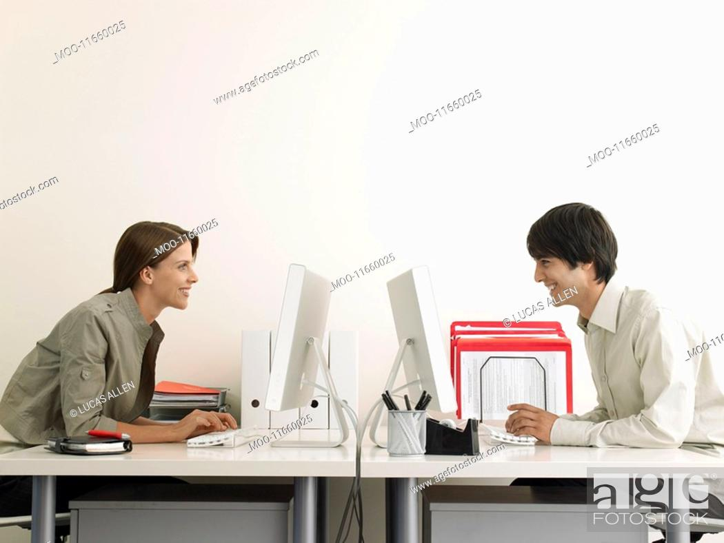 Stock Photo: Business Man and Woman Working on Computers Face to Face.