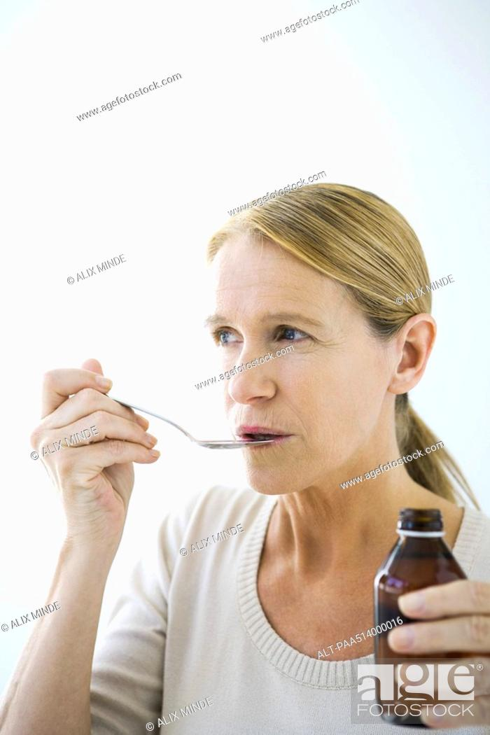 Stock Photo: Mature woman taking a spoonful of medicine.