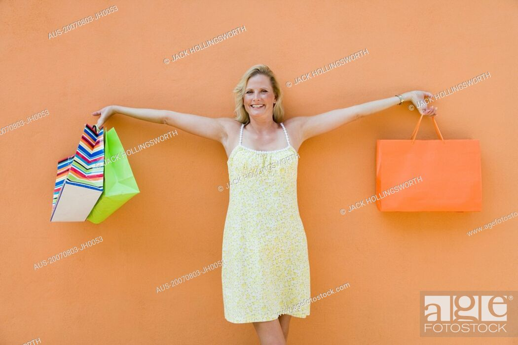 Stock Photo: Mature woman holding shopping bags with her arm outstretched and smiling.