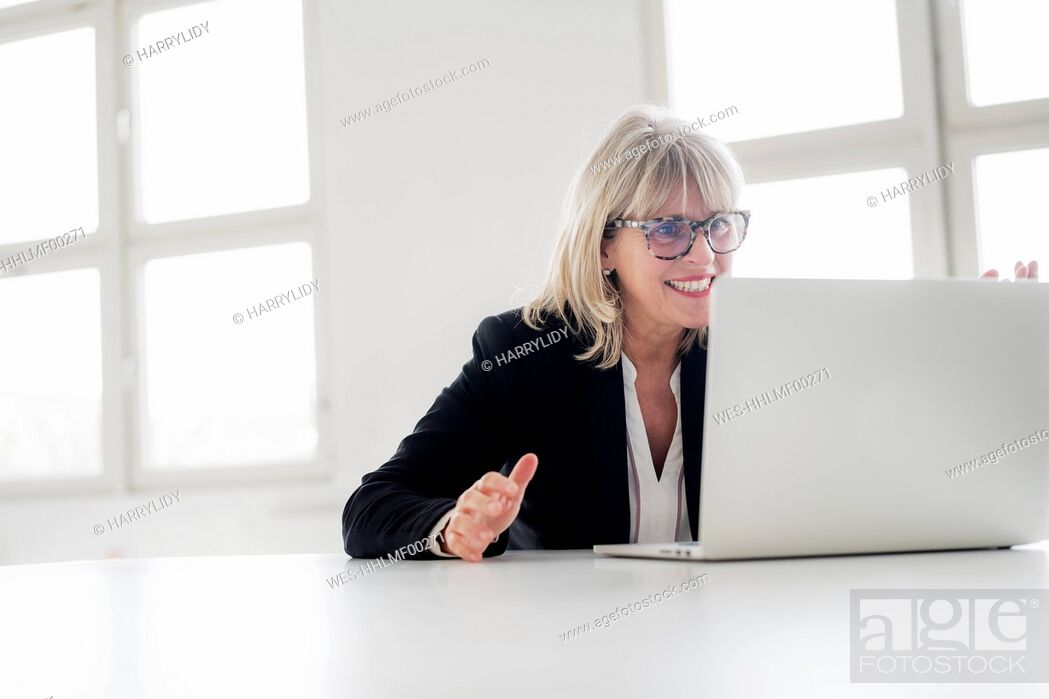 Stock Photo: Smiling mature businesswoman working on laptop at desk in the office.