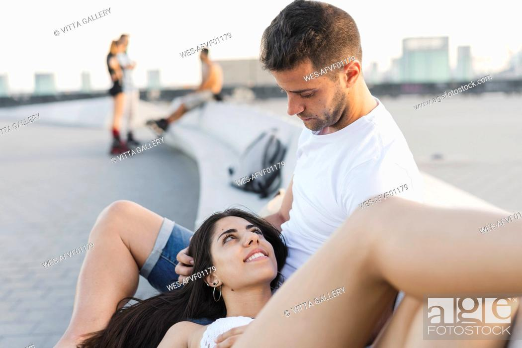 Stock Photo: Happy young woman lying on lap of her boyfriend, portrait.