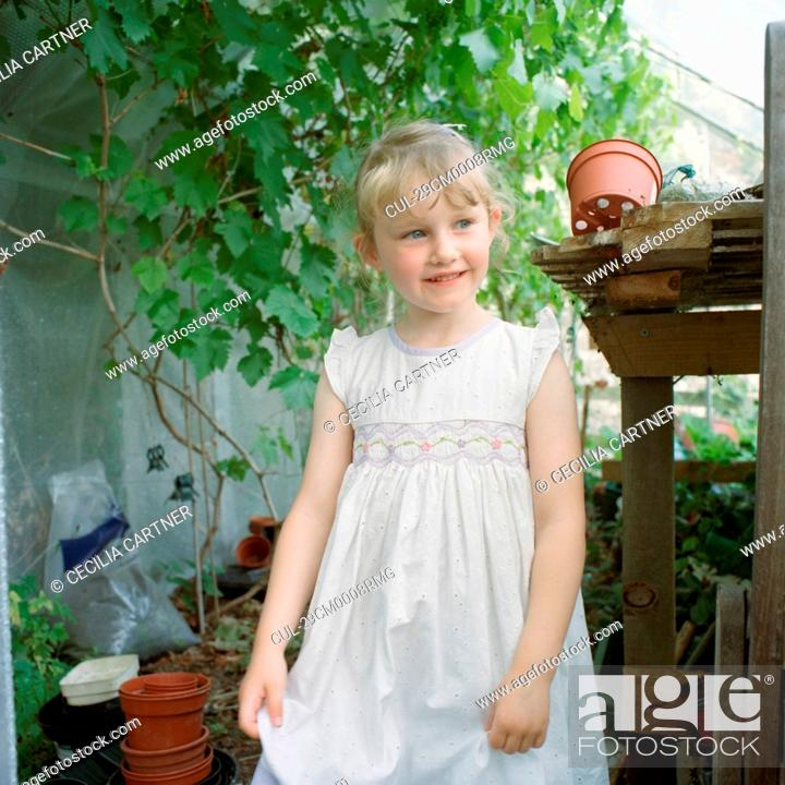 Stock Photo: Little girl in greenhouse.