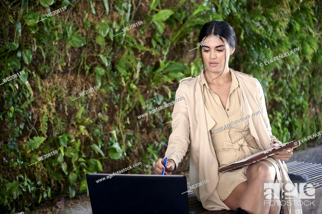 Photo de stock: Carefree and serene young European woman using her laptop while sitting in the urban park.