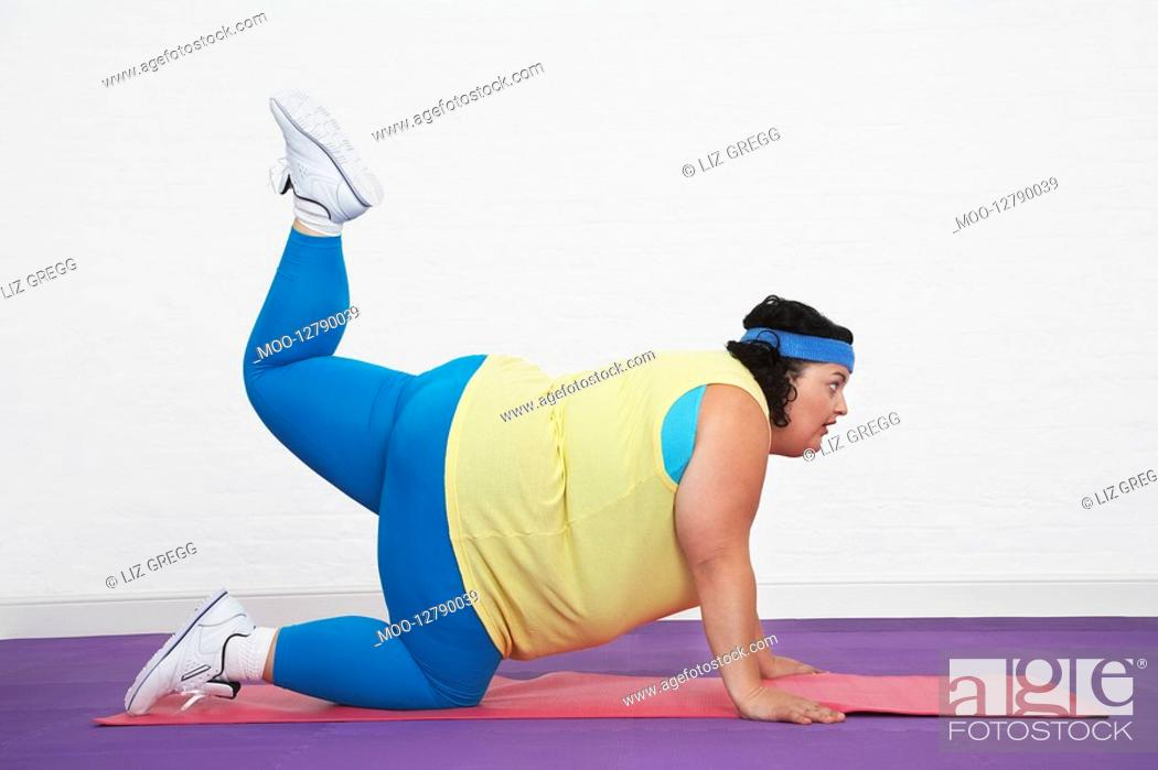 Stock Photo: Overweight Woman on floor doing aerobic stretches.