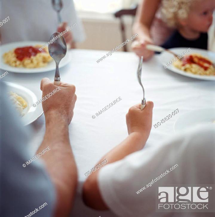 Stock Photo: Family eating spaghetti.