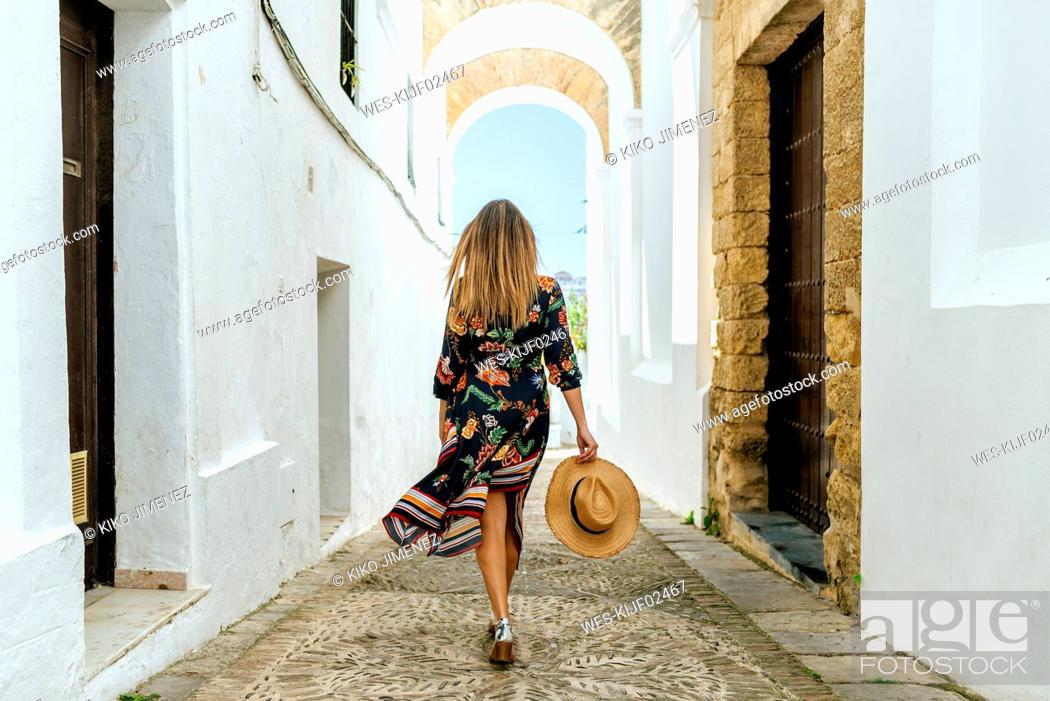 Stock Photo: Spain, Cadiz, Vejer de la Frontera, back view of fashionable woman walking through passage.