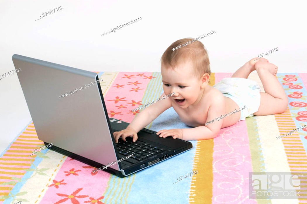 Stock Photo: Baby lying on tummy, wearing nappies, playing with laptop computer, Studio, Oetwil am See, Zuerich, Switzerland.