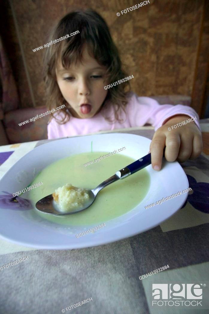 Stock Photo: Little Girl Making A Sour Face At Breakfast.