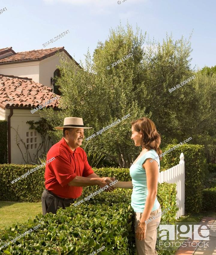 Stock Photo: Hispanic man and woman shaking hands over hedge.