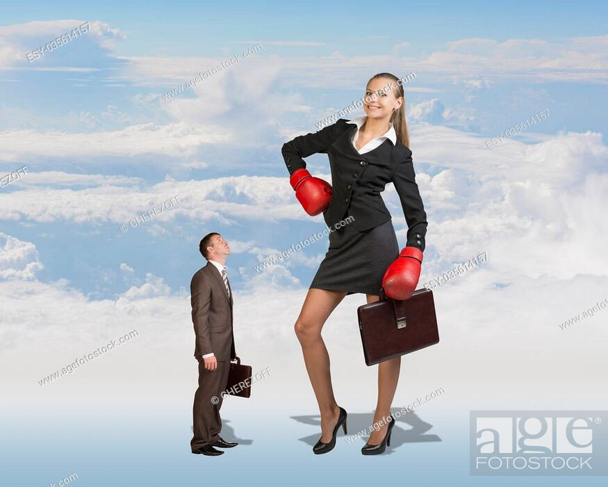 Stock Photo: Conceptual Small Serious Businessman Staring at Giant Smiling Businesswoman with Boxing Gloves and Briefcase on White Clouds Background.