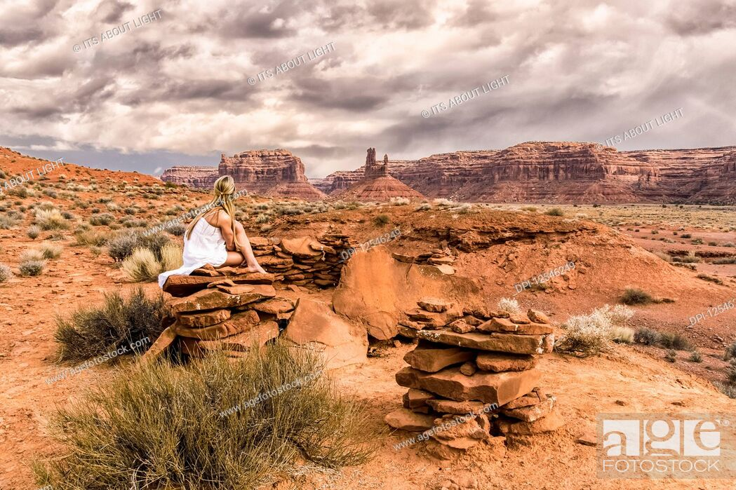 Stock Photo: A woman sits on a rock in the Valley of the Gods; Utah, United States of America.