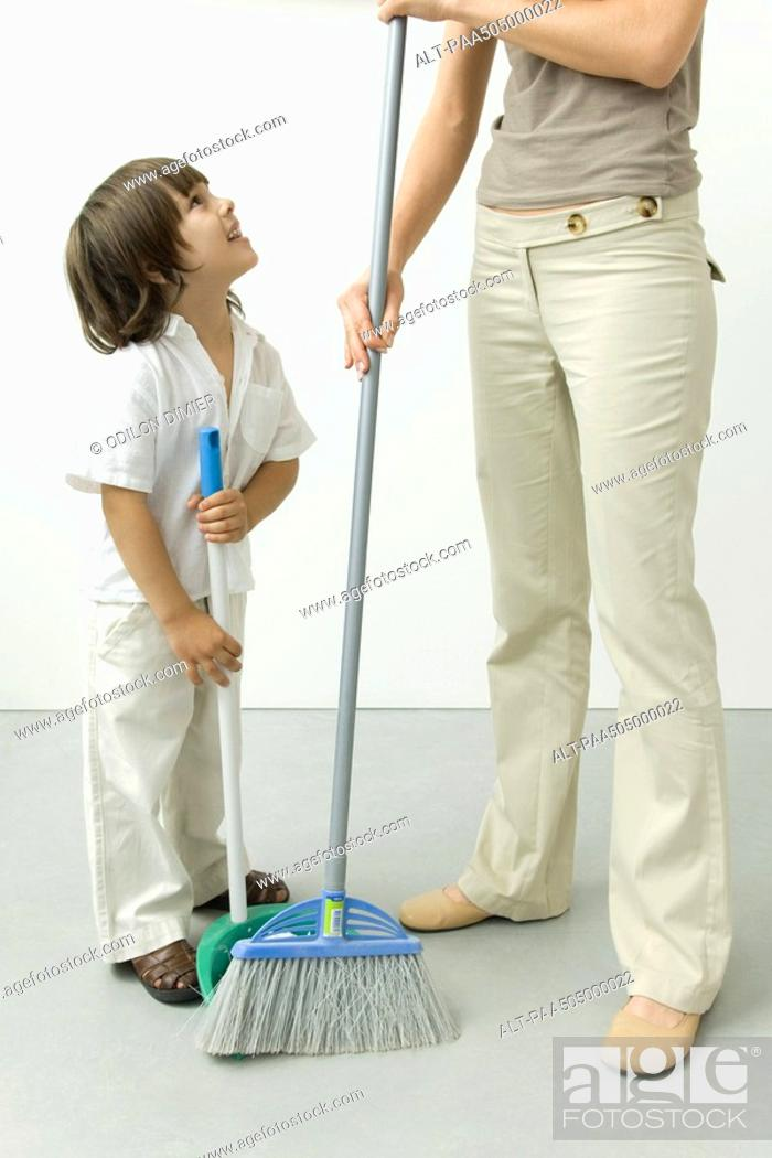 Stock Photo: Little boy helping his mother sweep the floor, cropped view.