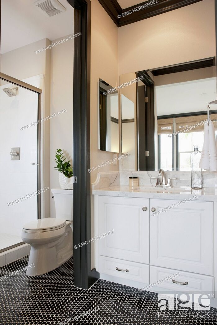 Imagen: White cabinets and washbasin with commode in the bathroom at home; Irvine; California; USA.