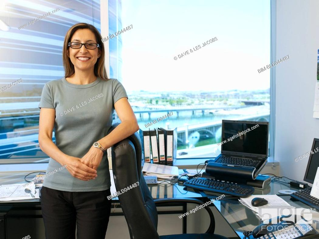 Stock Photo: Hispanic businesswoman leaning on chair.