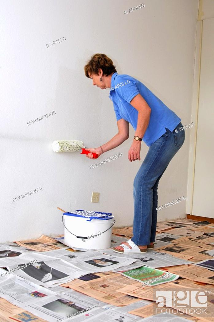 Stock Photo: Woman painting the walls of her apartement.