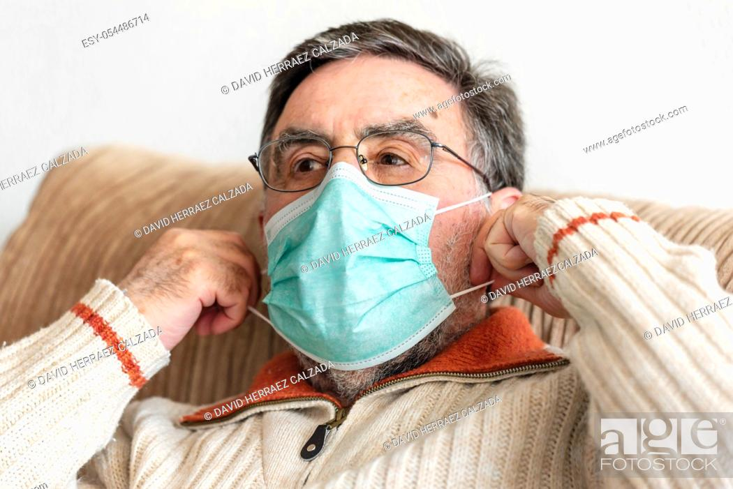 Stock Photo: Elderly man putting a medical mask on his face to protect himself from coronavirus pandemic .