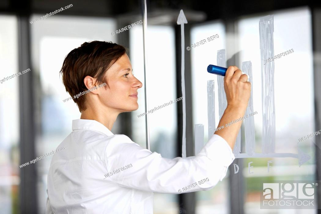 Stock Photo: Businesswoman drawing bar chart at glass pane in office.
