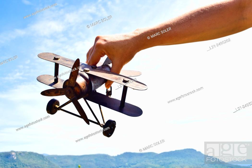 Stock Photo: Close-up of  hand holding a model airplane against sky and mountain range.