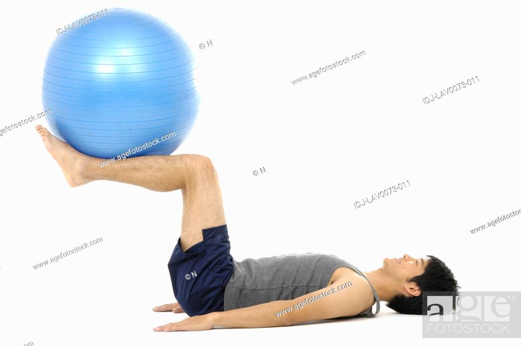 Stock Photo: Side profile of a young man exercising with a fitness ball.