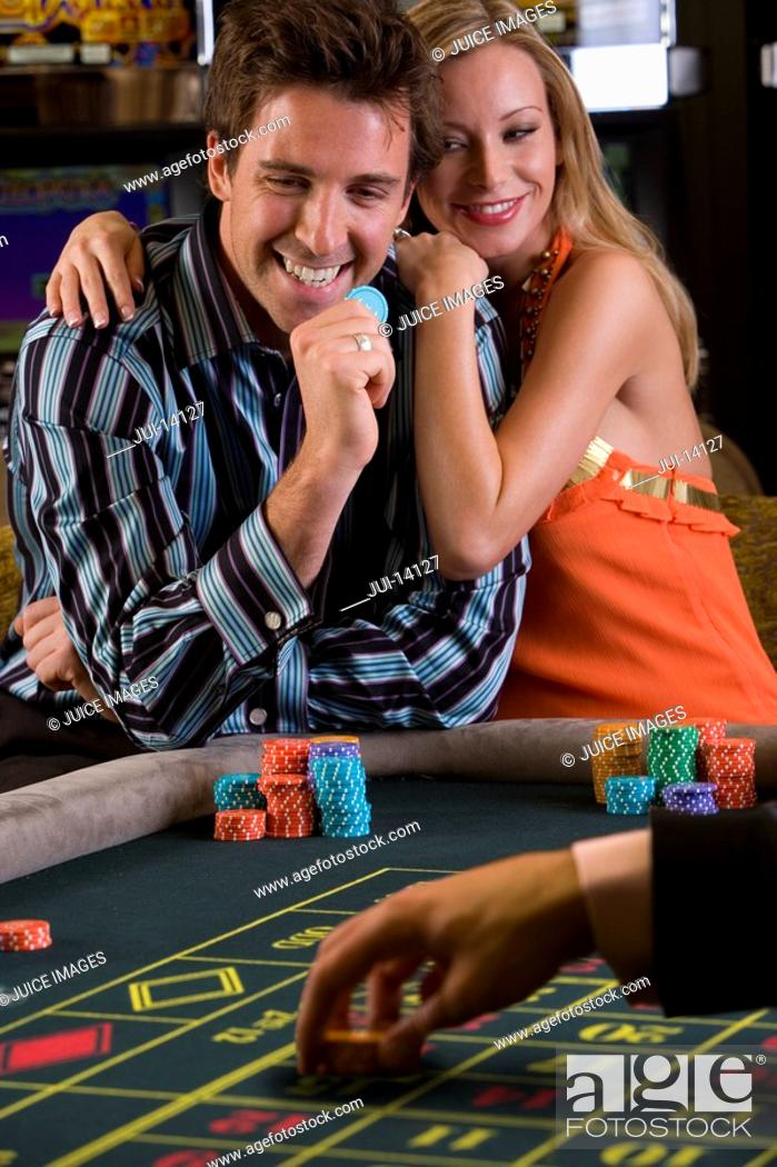 Stock Photo: Young couple gambling, man with gambling chip, smiling, portrait.