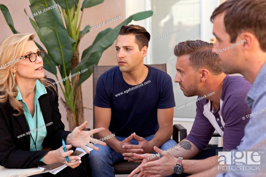Imagen: Men talking with therapist in group therapy.