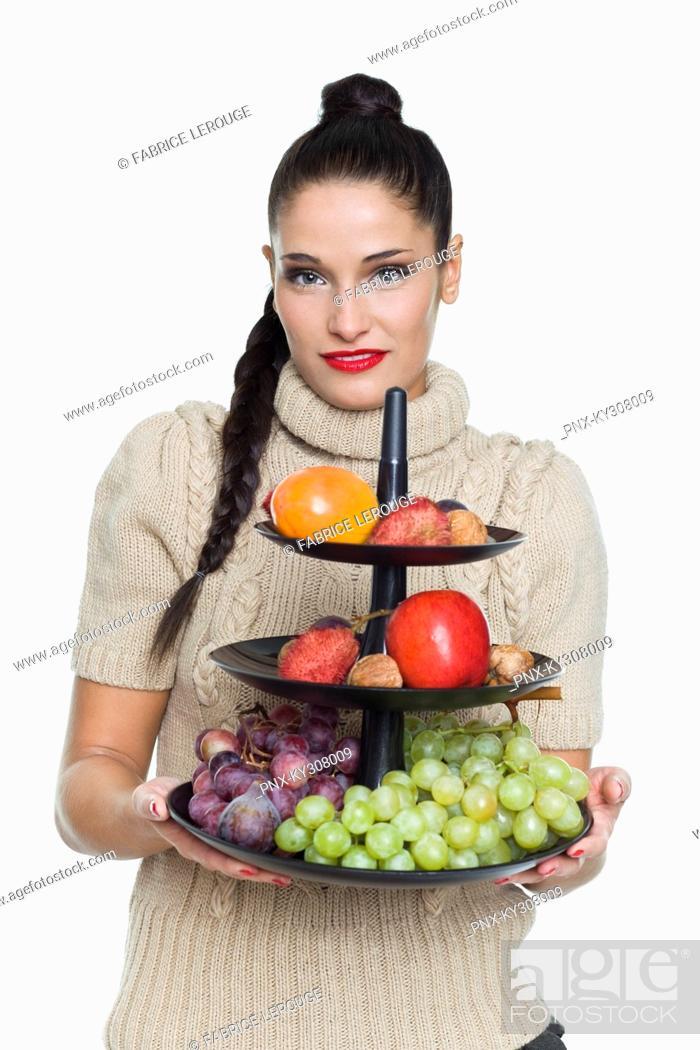 Photo de stock: Young woman holding fruit dish.