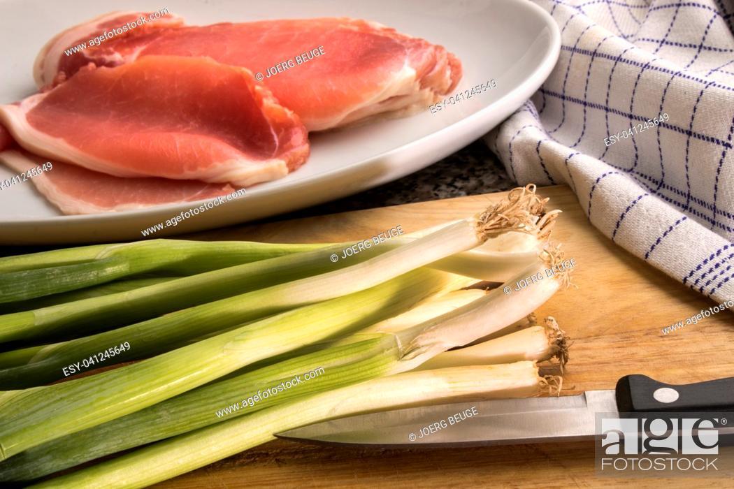 Stock Photo: organic spring onion and raw bacon on a wooden board to prepare irish colcannon.