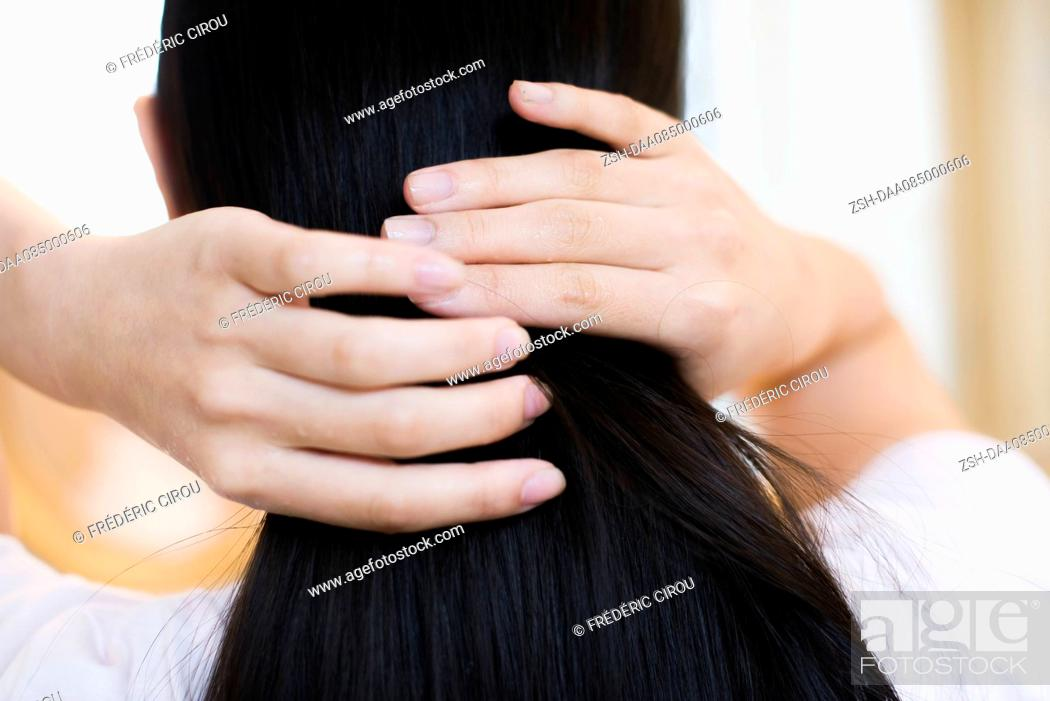Stock Photo: Woman fixing her hair, rear view.