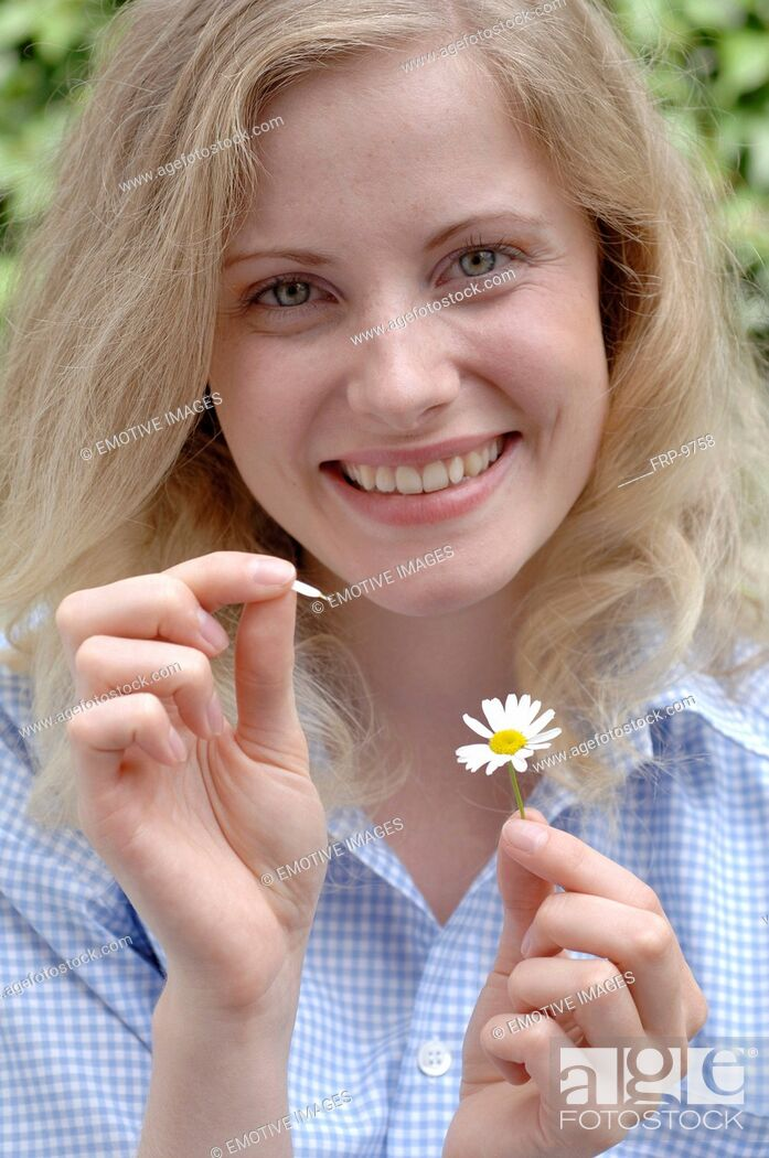 Imagen: Happy woman plucking petals from daisy.