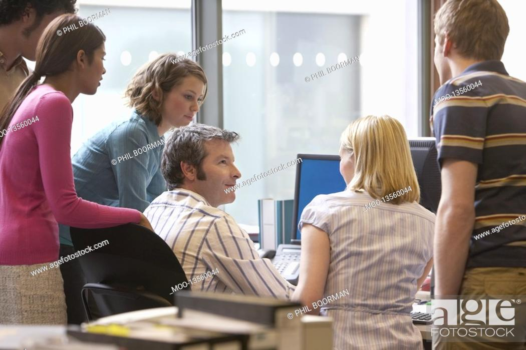 Stock Photo: Office workers standing around colleague using computer back view.