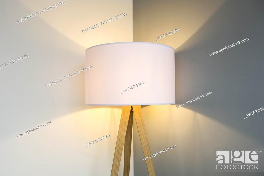 Stock Photo: floor lamp standing near white grey wall with big lamp shade modern design, symmetrical light background texture close-up.