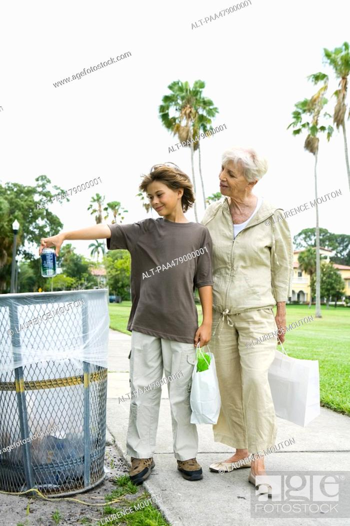Stock Photo: Boy and grandmother standing by trash can, boy throwing away drink can.