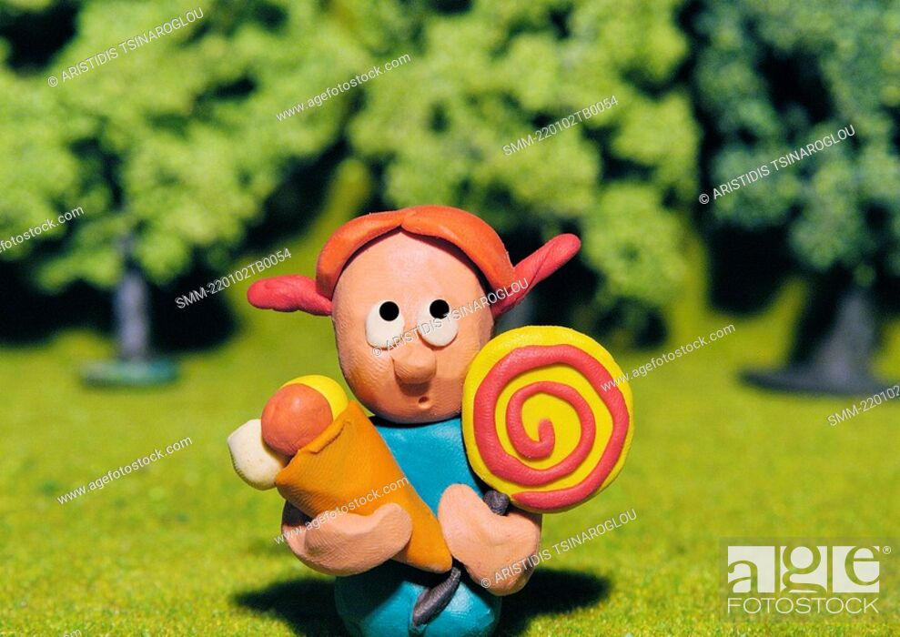 Stock Photo: Girl with ice cream and lollipop in park.