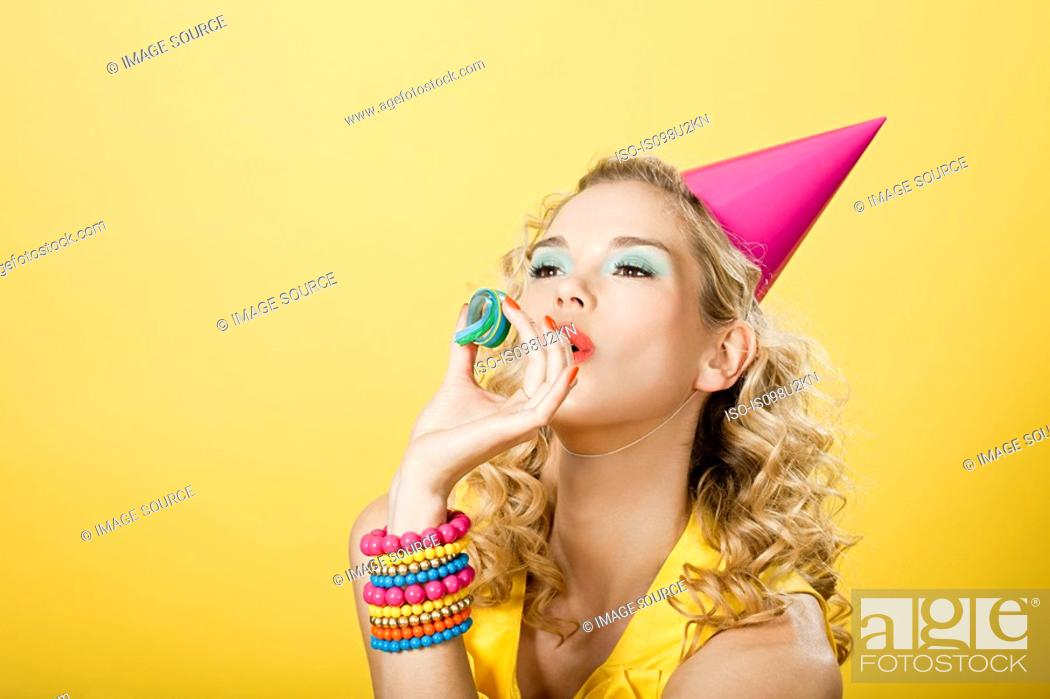 Stock Photo: Young woman wearing party hat with party streamer.